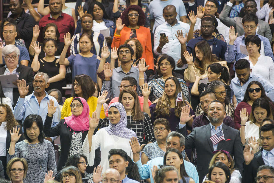 New citizens raise their hands to take the formal oath of allegiance to become naturalized United States citizens during a ceremony at the M.O. Campbell Education Center in Houston, Wednesday, July 10, 2019. Photo: Mark Mulligan / Houston Chronicle