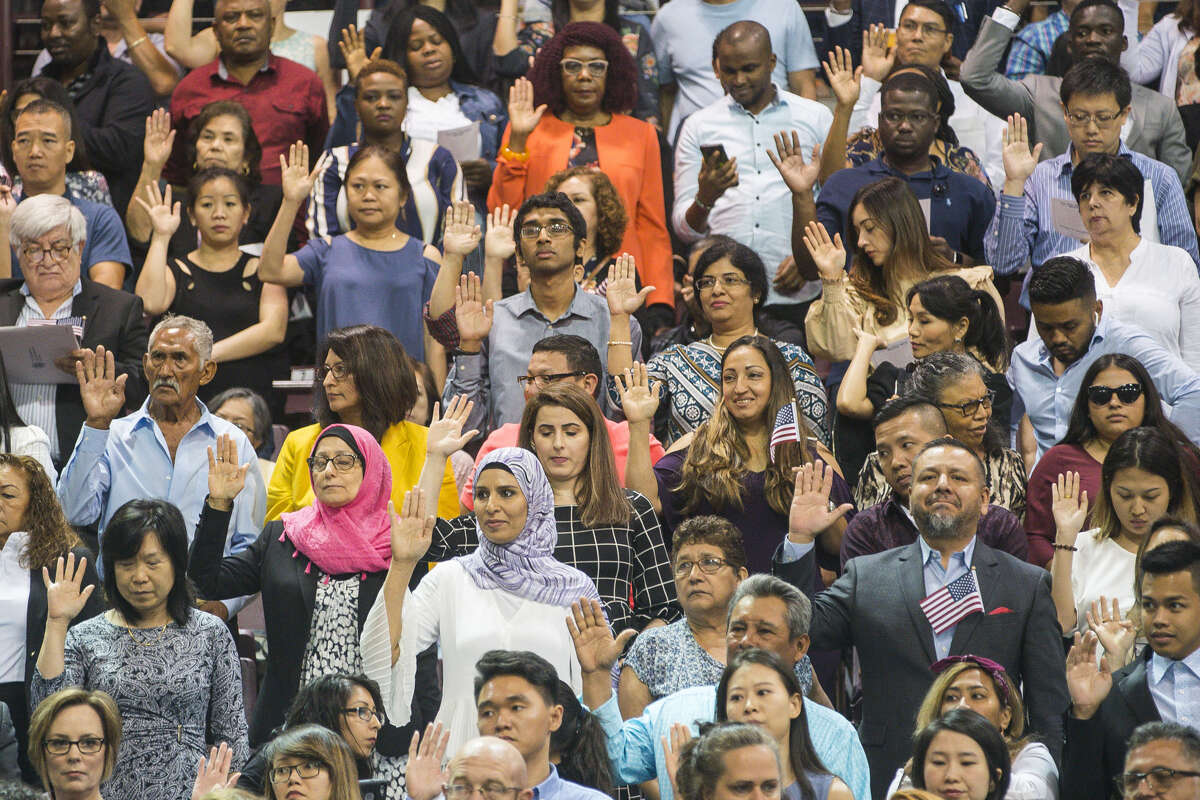 New citizens raise their hands to take the formal oath of allegiance to become naturalized United States citizens during a ceremony at the M.O. Campbell Education Center in Houston, Wednesday, July 10, 2019.