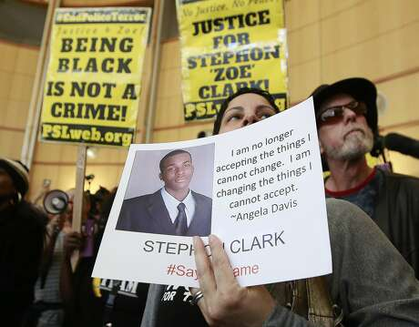 FILE - In this March 22, 2018, file photo, Anita Ross holds a photo of 22-year-old Stephon Clark, who was fatally shot by police, as she and other protesters block the entrance to Sacramento City Hall in Sacramento, Calif. A new report released Tuesday, July 2, 2019, by the state attorney general's office said the number of civilian deaths in police confrontations is down from each of the last two years, but included Stephon Clark, an unarmed black vandalism suspect killed by Sacramento police. (AP Photo/Rich Pedroncelli, File)