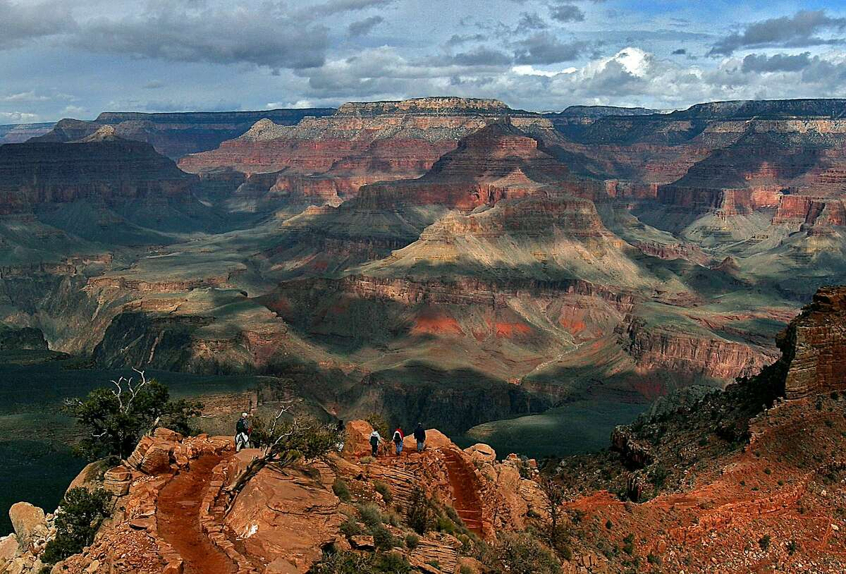 FILE -- With the North Rim in the background, tourists hike along the South Rim of the Grand Canyon in this Feb. 22, 2005 file photo in Grand Canyon, Ariz. . (AP Photo/Rick Hossman, File)