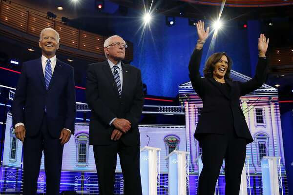 Democratic presidential candidates former vice president Joe Biden, left, Sen. Bernie Sanders, I-Vt., and Sen. Kamala Harris, D-Calif., right, stand on stage for a photo op before the start of the the Democratic primary debate hosted by NBC News at the Adrienne Arsht Center for the Performing Arts, Wednesday, June 27, 2019, in Miami. (AP Photo/Brynn Anderson)
