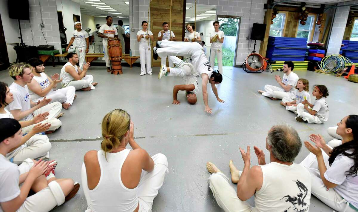 New Haven, Connecticut -Tuesday, July 16, 2019: Efrain Silva, the co-executive director of the Connecticut Capoeira & Dance Center in New Haven, bottom, and 13-year capoeira practioner Jeff Herdle of West Haven perform a routine during a capoeira class session.