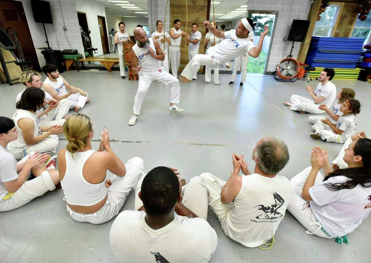 New Haven, Connecticut -Tuesday, July 16, 2019: Efrain Silva, the co-executive director of the Connecticut Capoeira & Dance Center in New Haven, bottom, and 12-year capoeira practitioner Daniel Carbajal (CQ) of Hamden perform a routine during a capoeira class session.