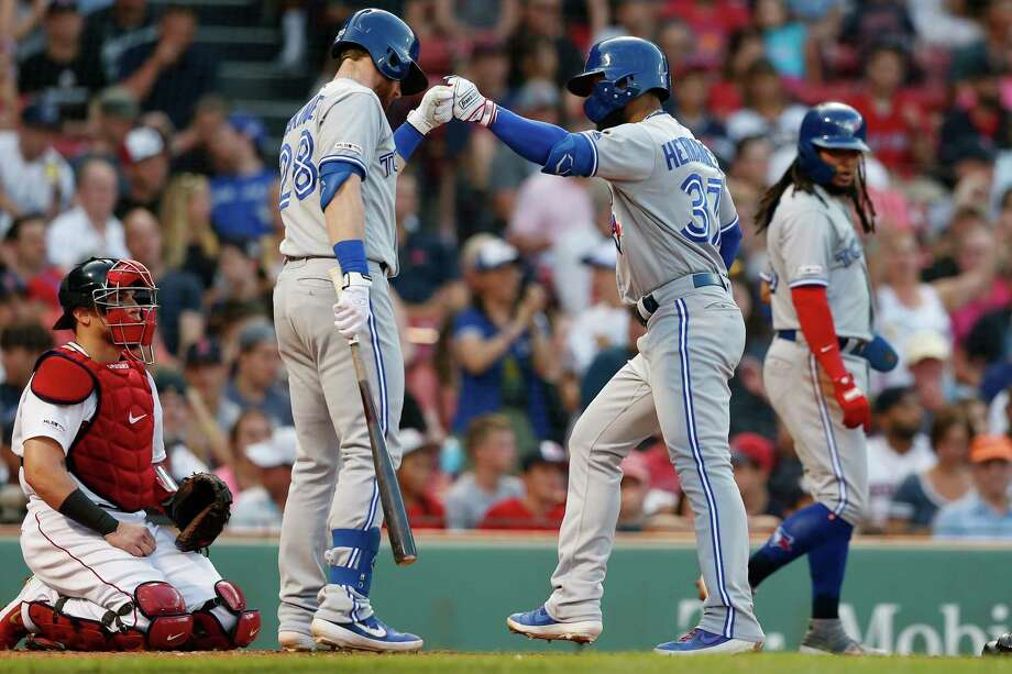 Toronto Blue Jays' Teoscar Hernandez (37) celebrates his three-run home run with Billy McKinney (28) as Boston Red Sox's Christian Vazquez, left, kneels behind the plate during the second inning of a baseball game in Boston, Tuesday, July 16, 2019. (AP Photo/Michael Dwyer) Photo: Michael Dwyer / Copyright 2019 The Associated Press. All rights reserved