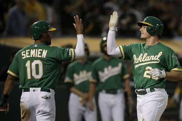 Oakland Athletics' Matt Chapman, right, celebrates with Marcus Semien (10) after hitting a two-run home run off Seattle Mariners' Marco Gonzales during the fifth inning of a baseball game Tuesday, July 16, 2019, in Oakland, Calif. (AP Photo/Ben Margot)
