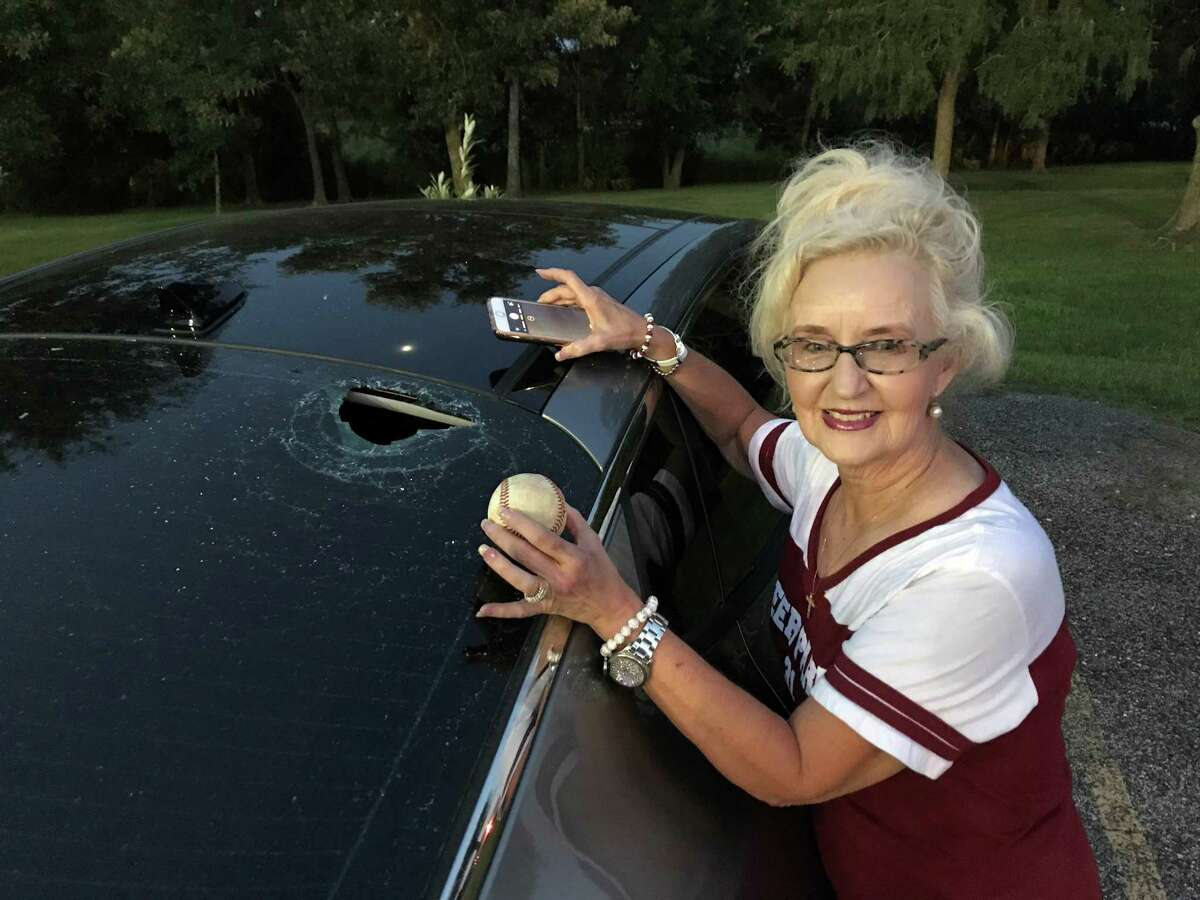 While holding the baseball that did all the damage, Dixie Davidson poses next to her shattered back window that was caused by a foul ball hit by her grandson.