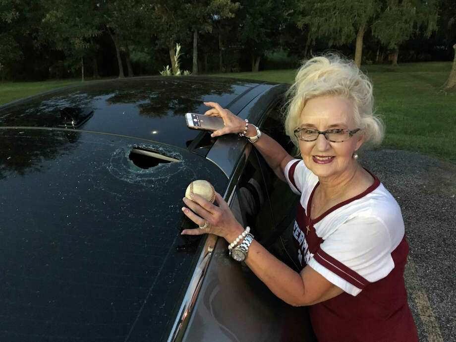 While holding the baseball that did all the damage, Dixie Davidson poses next to her shattered back window that was caused by a foul ball hit by her grandson. Photo: Robert Avery