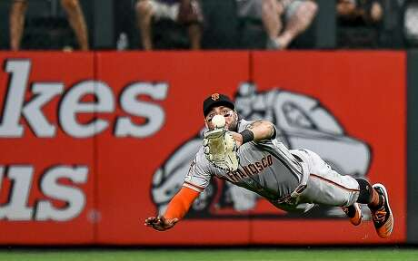 Kevin Pillar of the Giants makes the first of two diving grabs in center field in the eighth against the Rockies at Coors Field. He made another in the 10th. Photo: Dustin Bradford / Getty Images