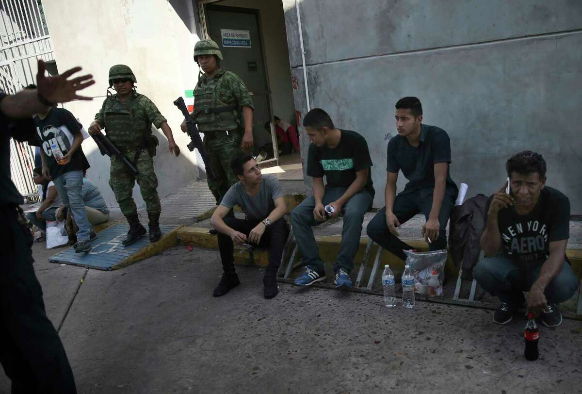 Migrants wait under guard at an immigration center on the International Bridge 1, as an immigration agent attempts to block the camera, in Nuevo Laredo, Mexico, Tuesday, July 16, 2019. A U.S. policy to make asylum seekers wait in Mexico while their cases wind through clogged U.S. immigration courts has also expanded to the violent city of Nuevo Laredo. The group was returned from the U.S. after being detained.