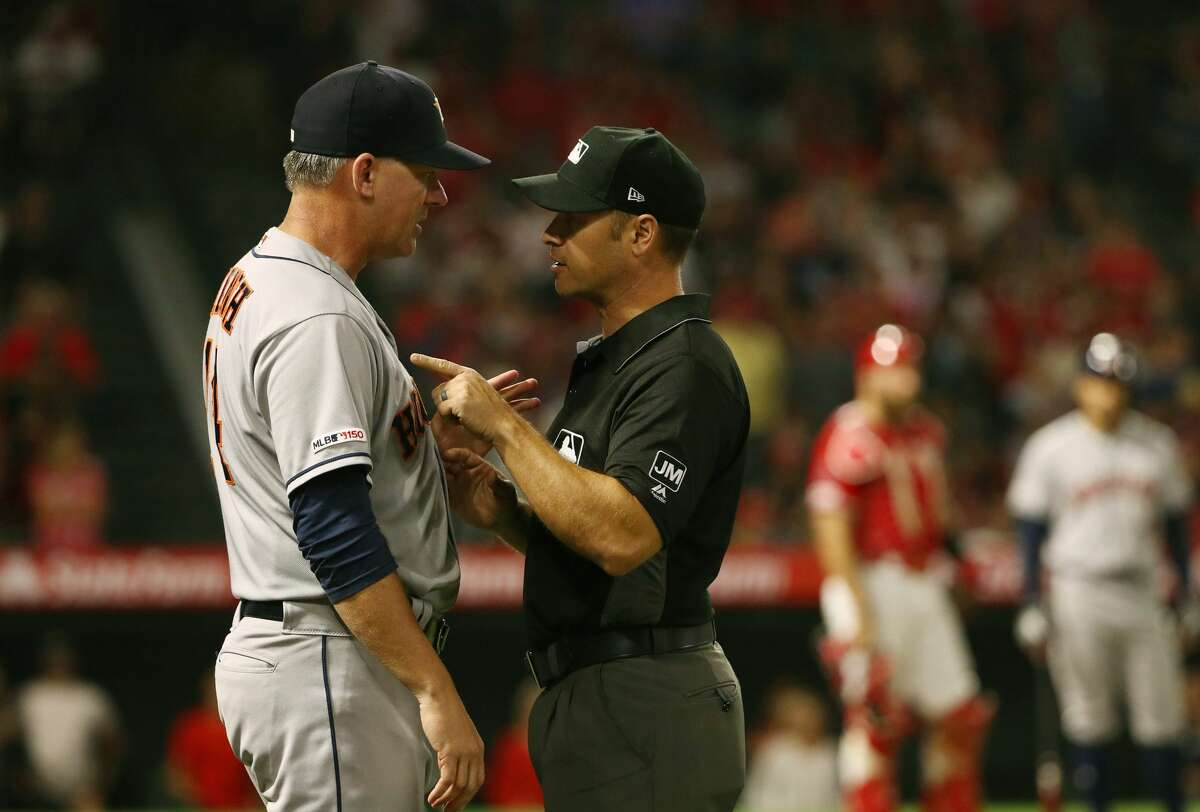 ANAHEIM, CALIFORNIA - JULY 16: Manager AJ Hinch #14 of the Houston Astros talks with first base umpire Mark Wegner during the sixth inning against the Los Angeles Angels at Angel Stadium of Anaheim on July 16, 2019 in Anaheim, California. (Photo by Victor Decolongon/Getty Images)