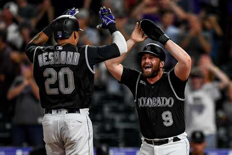 DENVER, CO - JULY 16: Ian Desmond #20 and Daniel Murphy #9 of the Colorado Rockies celebrate scoring on a Desmond home run, tying the game in the ninth inning against the San Francisco Giants at Coors Field on July 16, 2019 in Denver, Colorado. (Photo by Dustin Bradford/Getty Images) Photo: Dustin Bradford / Getty Images