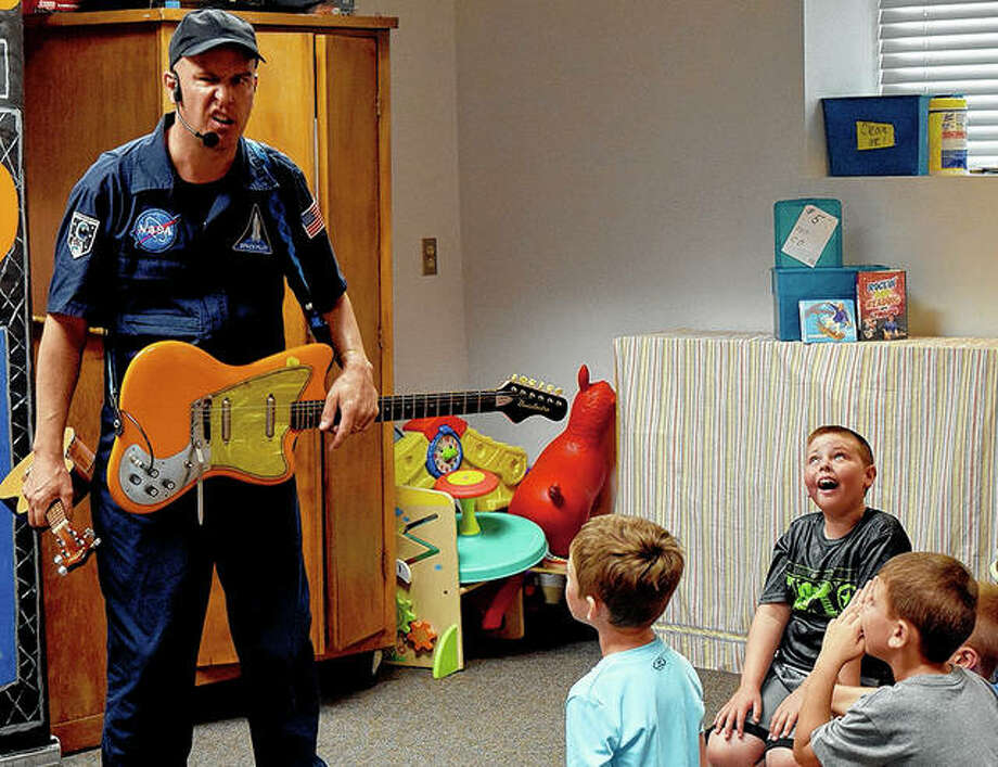 Children's performer Leonardo sings about the alphabet and his love of reading during a program Tuesday at the Jacksonville Public Library. Photo: Marco Cartolano | Journal-Courier