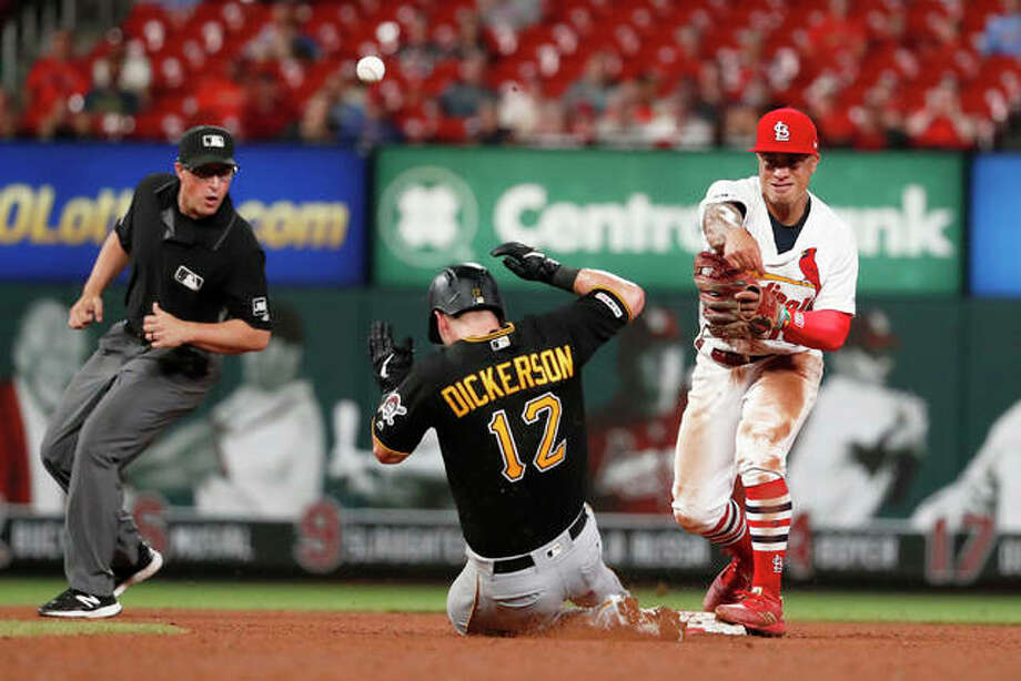The Pirates' Corey Dickerson (12) is out at second as Cardinals second baseman Kolten Wong (right) is unable to turn the double play during the ninth inning Tuesday in St. Louis. Watching is second base umpire Quinn Wolcott. Photo: AP