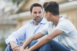 A father sitting with his serious 13 year old teenage son on the curb in front of their house.