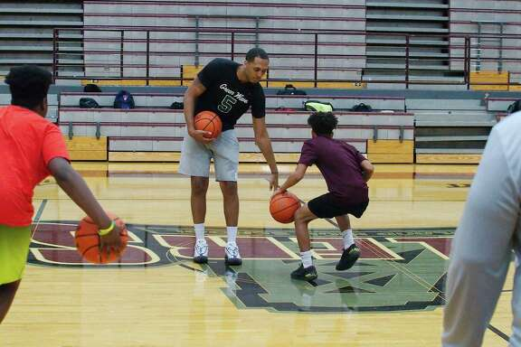 Former Pearland High School and ex-Minnesota Timberwolves player Cameron Reynolds gives pointers to Adolphus Evans Tuesday at the Pearland summer basketball camp.