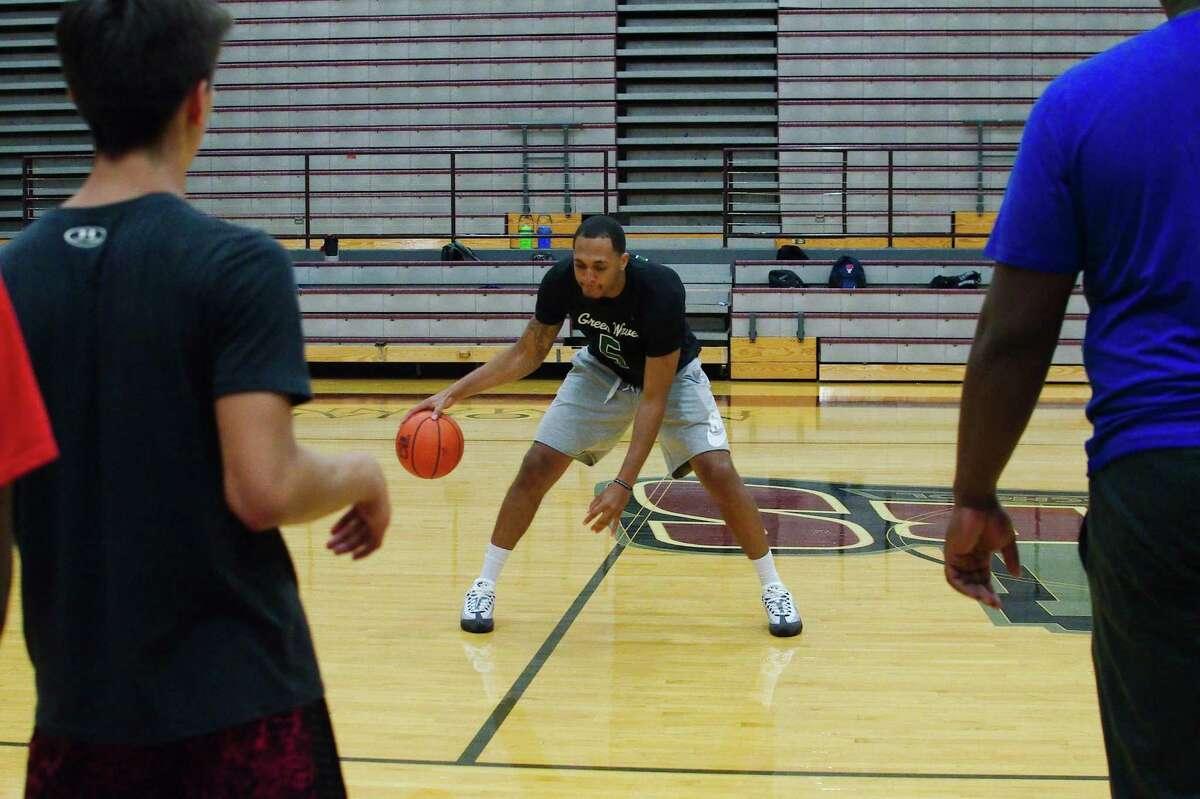 Former Pearland and ex-Minnesota Timberwolves players Cameron Reynolds demonstrates a drill at the Pearland summer basketball camp.