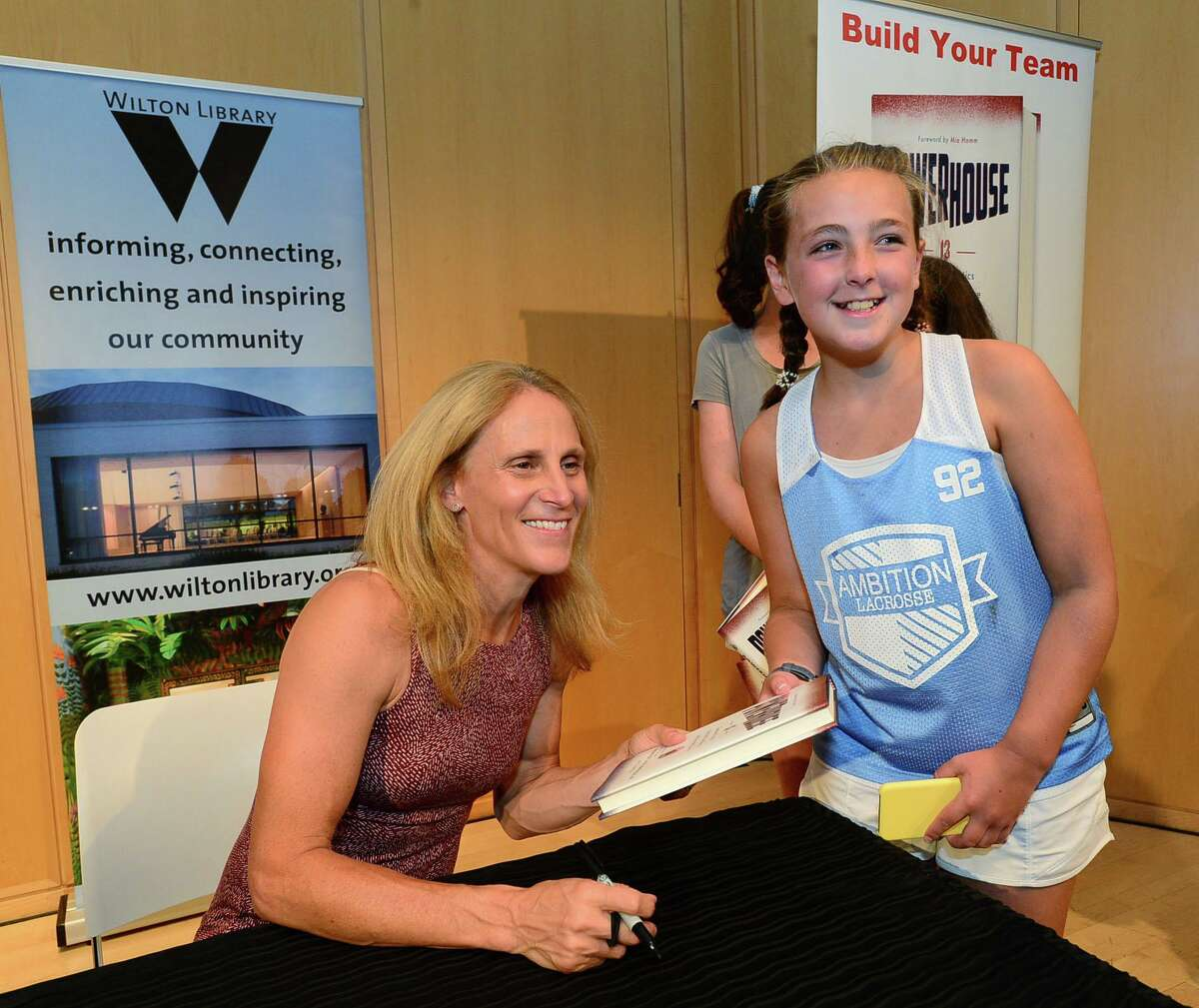 Wilton resident Annalise Lamanna, 12, gets a book signed by Wilton High School graduate and soccer star Kristine Lilly.