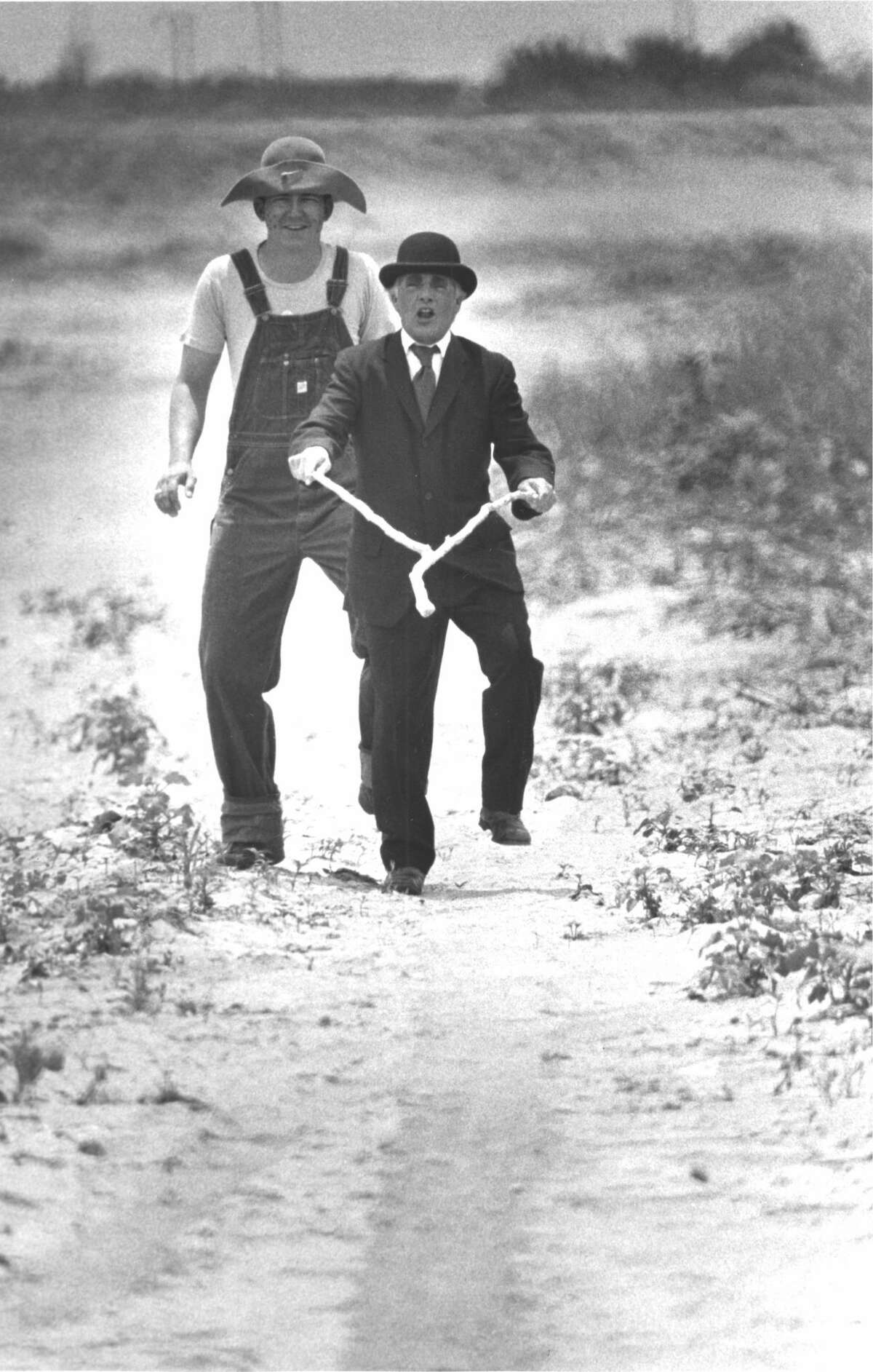File photos from past years of Summer Mummers. Summer Mummers hero Ron Hughes uses a divining rod to find oil while sidekick Dough Heck tags along to help. June 1984.