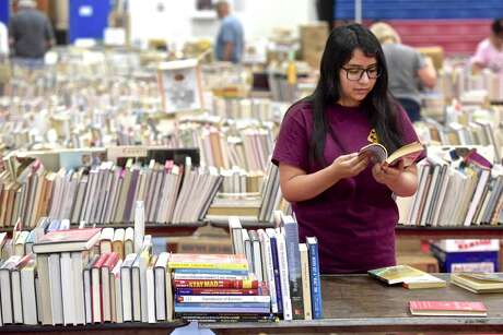 Jess Mendieta, a junior from Henry Abbott Technical High School, helps setup for the Friends of the Danbury Library Book Sale. The popularity of paperback and hardcover books has not been threatended by e-books — paper continues to endure.