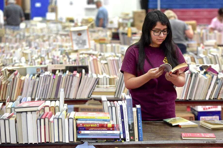 Jess Mendieta, a junior from Henry Abbott Technical High School, helps setup for the Friends of the Danbury Library Book Sale. The popularity of paperback and hardcover books has not been threatended by e-books — paper continues to endure. Photo: H John Voorhees III /Hearst Connecticut Media / The News-Times
