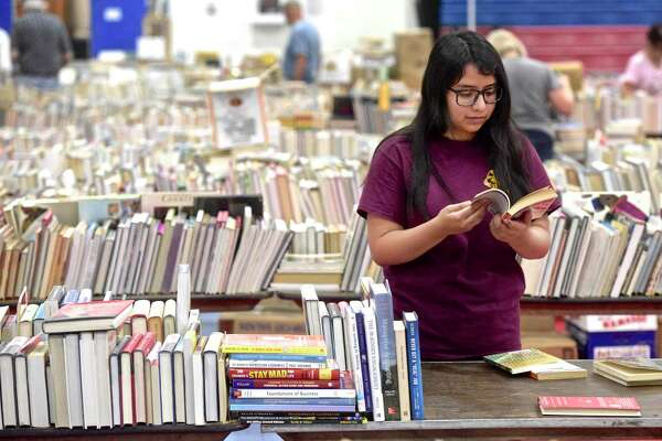 Jess Mendieta, a junior from Henry Abbott Technical High School, helps setup for the Friends of the Danbury Library Book Sale. The popularity of paperback and hardcover books has not been threatended by e-books - paper continues to endure.