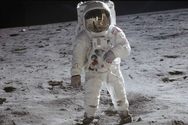 Astronaut Buzz Aldrin is photographed on the surface of the moon. Fellow astronaut Neil Armstrong, who took the photo, is reflected in Aldrin's visor.