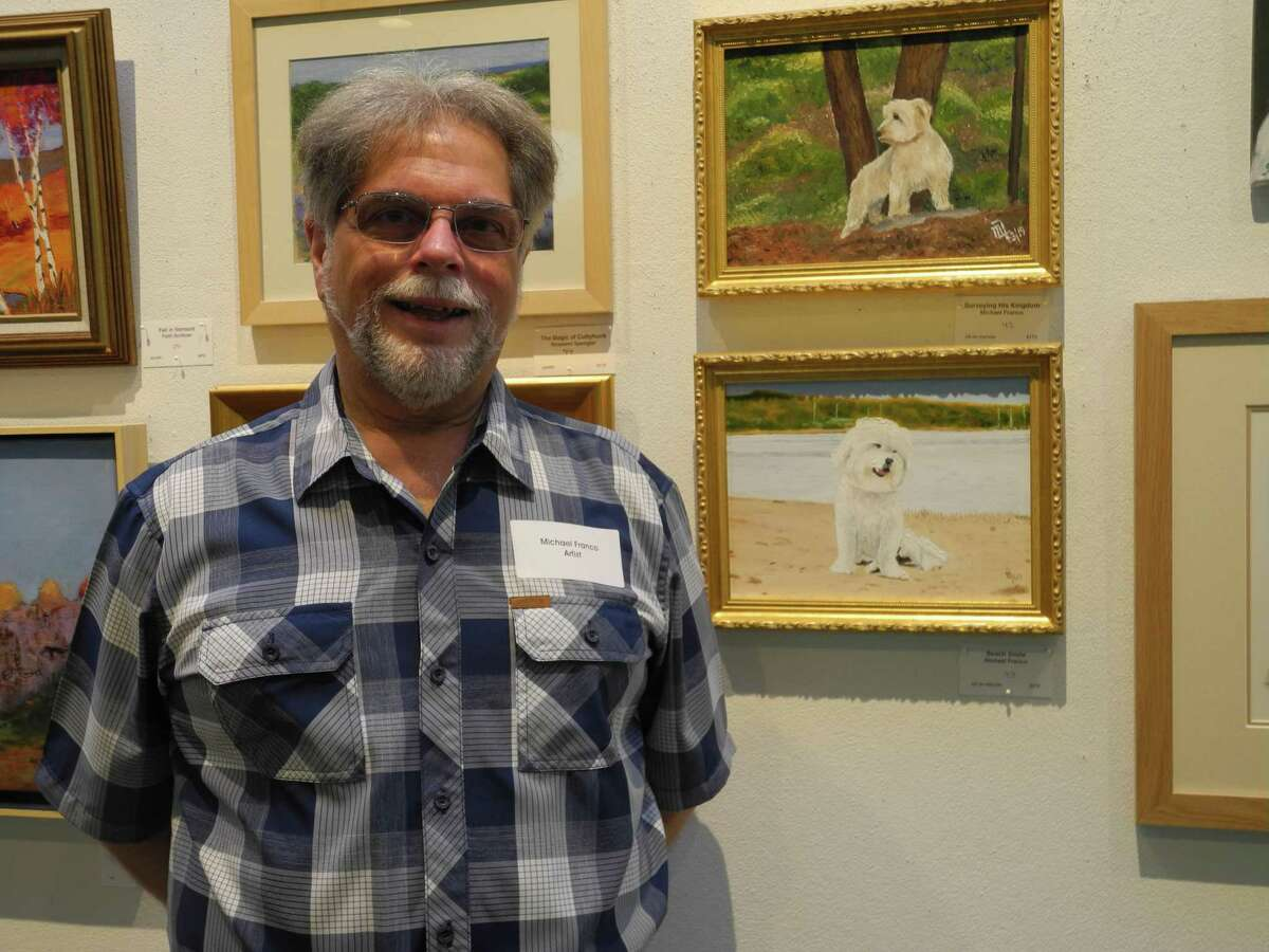 Michael Franco with portraits of two of the dogs he and his wife Mary Anne have owned that he entered in the Summer Show at Wilton Library. Wilton, Conn., July 12, 2019.