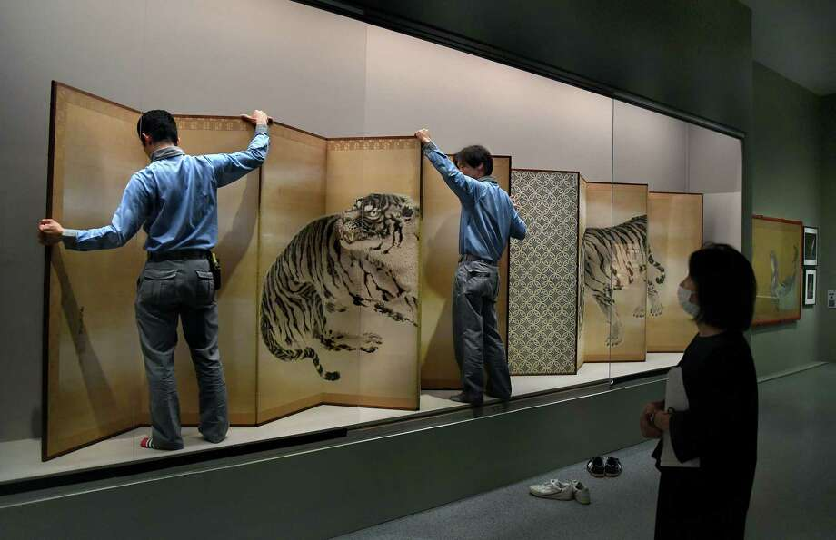 """Tomoko Matsuo, right, a senior curator of the Chiba City Museum of Art in Japan, watches as large panels are moved for the National Gallery of Art's """"The Life of Animals in Japanese Art"""" exhibition. Photo: Washington Post Photo By Michael S. Williamson / The Washington Post"""