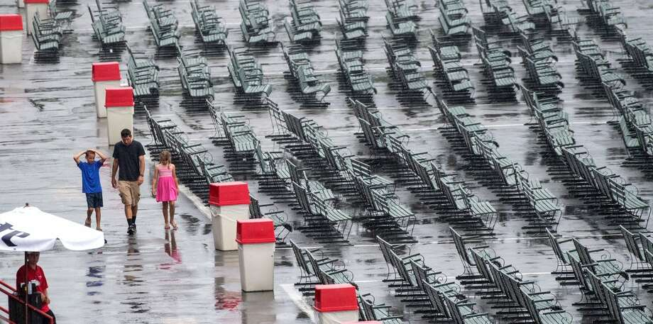 Race fans walk the track apron on Wednesday, July 17, 2019, at Saratoga Race Course. Rain canceled the first race and moved all turf races to the dirt track. (Skip Dickstein) Photo: Skip Dickstein