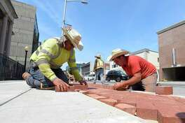 Rafael Cruz and Simone Rossi lay bricks, that are part of a decorative edging to a new sidewalk along Summer Street in Stamford, Conn. on July 16, 2019. The crew from Colonna Concrete and Asphalt Paving out of West Haven each were wearing large straw caps to help shade themselves from the heat of the sun. Temperatures in the region reach into the 90's with no expected relief in the coming days.