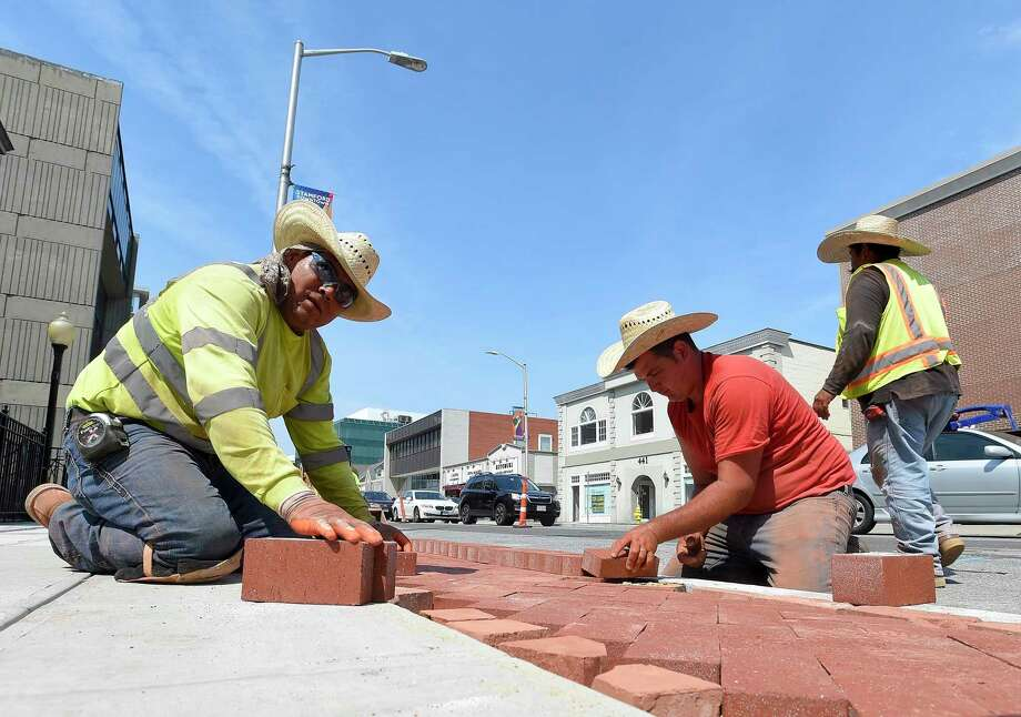 Rafael Cruz and Simone Rossi lay bricks, that are part of a decorative edging to a new sidewalk along Summer Street in Stamford, Conn. on July 16, 2019. The crew from Colonna Concrete and Asphalt Paving out of West Haven each were wearing large straw caps to help shade themselves from the heat of the sun. Temperatures in the region reach into the 90's with no expected relief in the coming days. Photo: Matthew Brown / Hearst Connecticut Media / Stamford Advocate