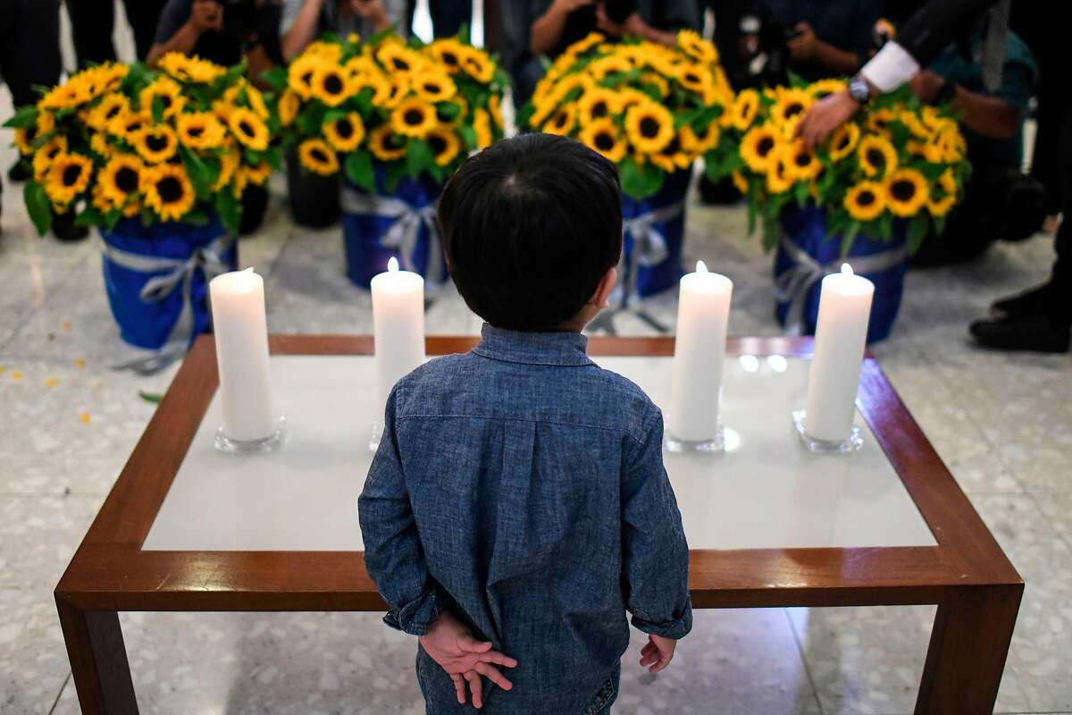 A boy stands in front of candles and flowers during a commemoration ceremony for passengers who perished aboard flight Malaysia Airlines flight MH17, which was shot down over eastern Ukraine five years ago at the Australian High Commission in Kuala Lumpur on July 17, 2019. (Photo by MOHD RASFAN / AFP)MOHD RASFAN/AFP/Getty Images