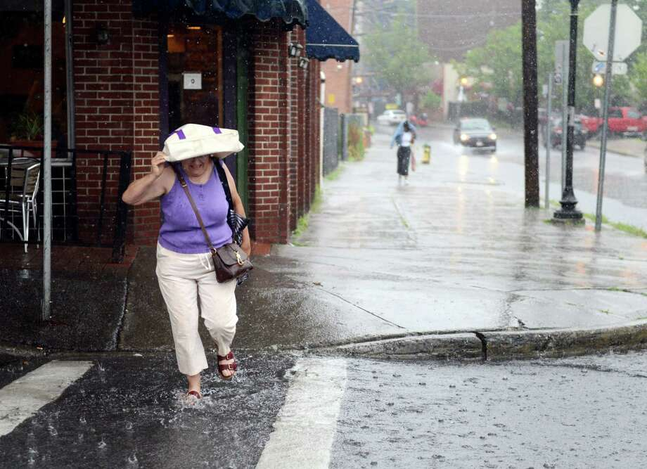 Carol Murphy of Rotterdam wades through deep water on the corner of Phila St. and Putnam St. on Wednesday, July 17, 2019, in Saratoga Springs, N.Y. (Catherine Rafferty/Times Union) Photo: Catherine Rafferty, Albany Times Union