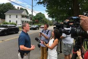 Police speak to the media after the body of a man was pulled from the Naugatuck River in Torrington.