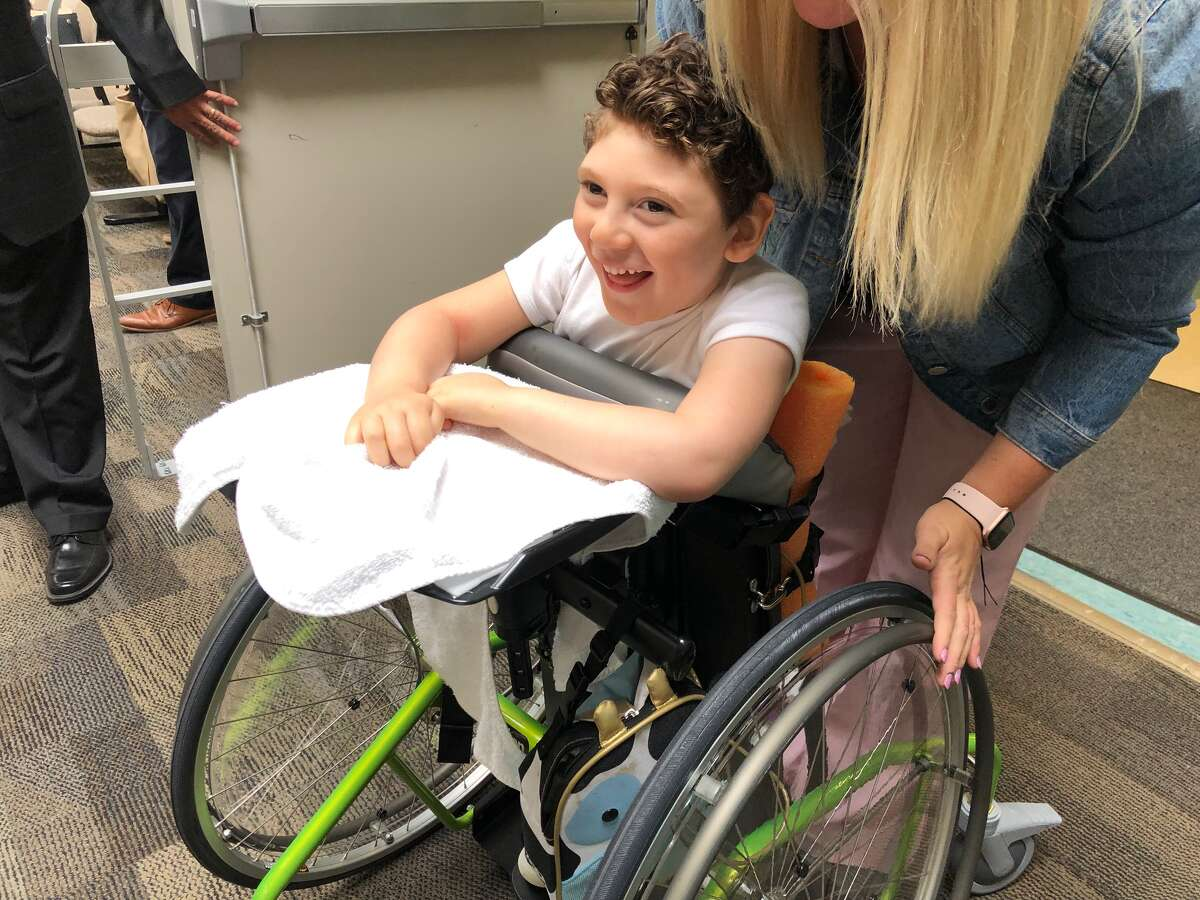 Miles Robinson,5, is a student at Clover Patch Preschool. He uses a walker equipped with supports and over-sized wheels to help him stand upright and learn to steer himself.