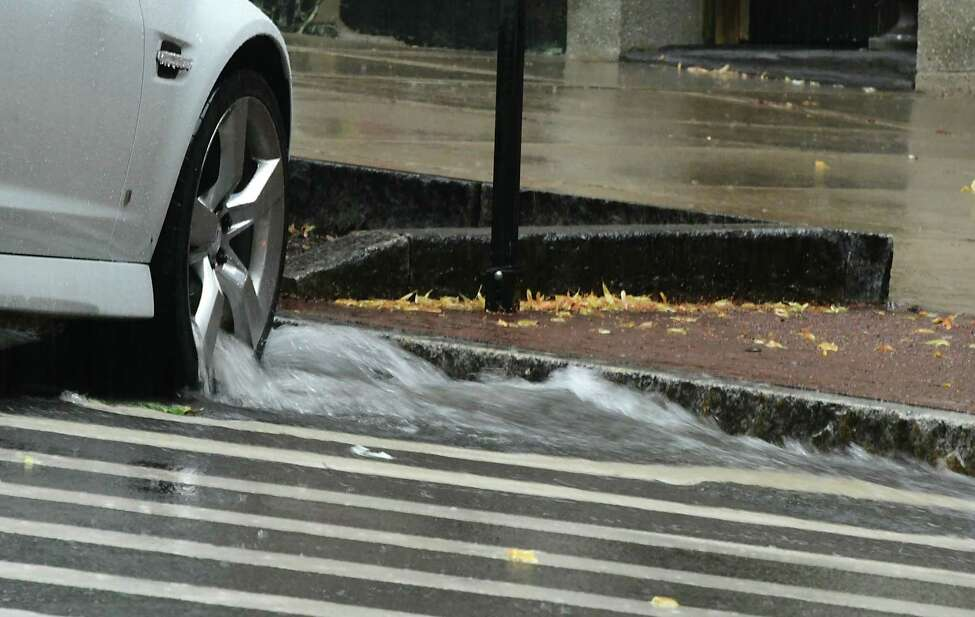 Water rushes through tires on a car parked on State St. during a rain downpour on Wednesday, July 17, 2019 in Albany, N.Y. (Lori Van Buren/Times Union)