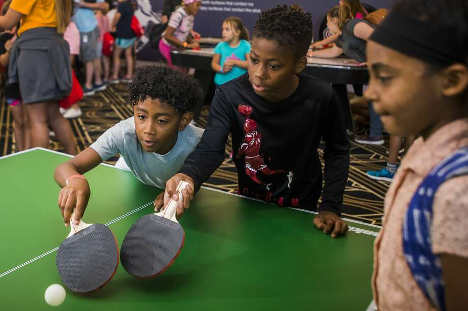 Armani Wright of Bay City, 8, left, and Cornelius Turner of Bay City, 11, center, play ping pong during the STEM in Sports event on Wednesday, July 17, 2019 at the Midland Country Club. For more photos, go to www.ourmidland.com. (Katy Kildee/kkildee@mdn.net) Photo: (Katy Kildee/kkildee@mdn.net)
