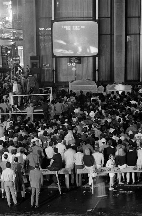 People gather at the Time-Life Building in New York's Rockefeller Center to watch as Neil Armstrong takes his first step on the moon on July 20, 1969. (Barton Silverman | The New York Times)