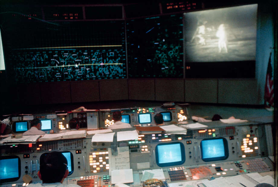 Flight controllers inside Mission Control monitor astronauts Neil Armstrong and Buzz Aldrin as they walk on the moon during the Apollo 11 mission on July 20, 1969. (NASA)