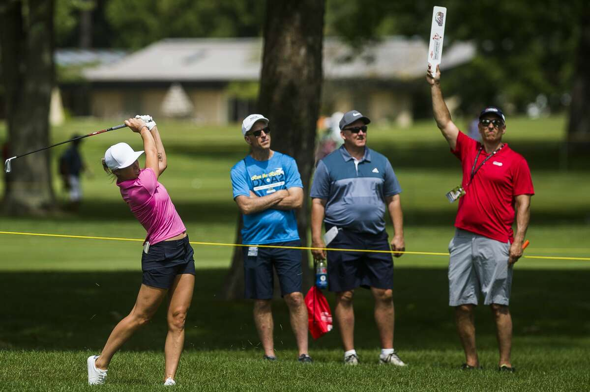 """A volunteer holds up a """"Quiet"""" sign as Mel Reid of England competes in the Dow Great Lakes Bay Invitational on Wednesday, July 17, 2019 at Midland Country Club. (Katy Kildee/kkildee@mdn.net)"""