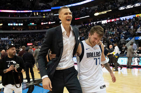 Dallas Mavericks forward Luka Doncic (77) hugs teammate Kristaps Porzingis as they walk off the floor following a victory against the Portland Trail Blazers on February 10, 2019 ,at American Airlines Center in Dallas.