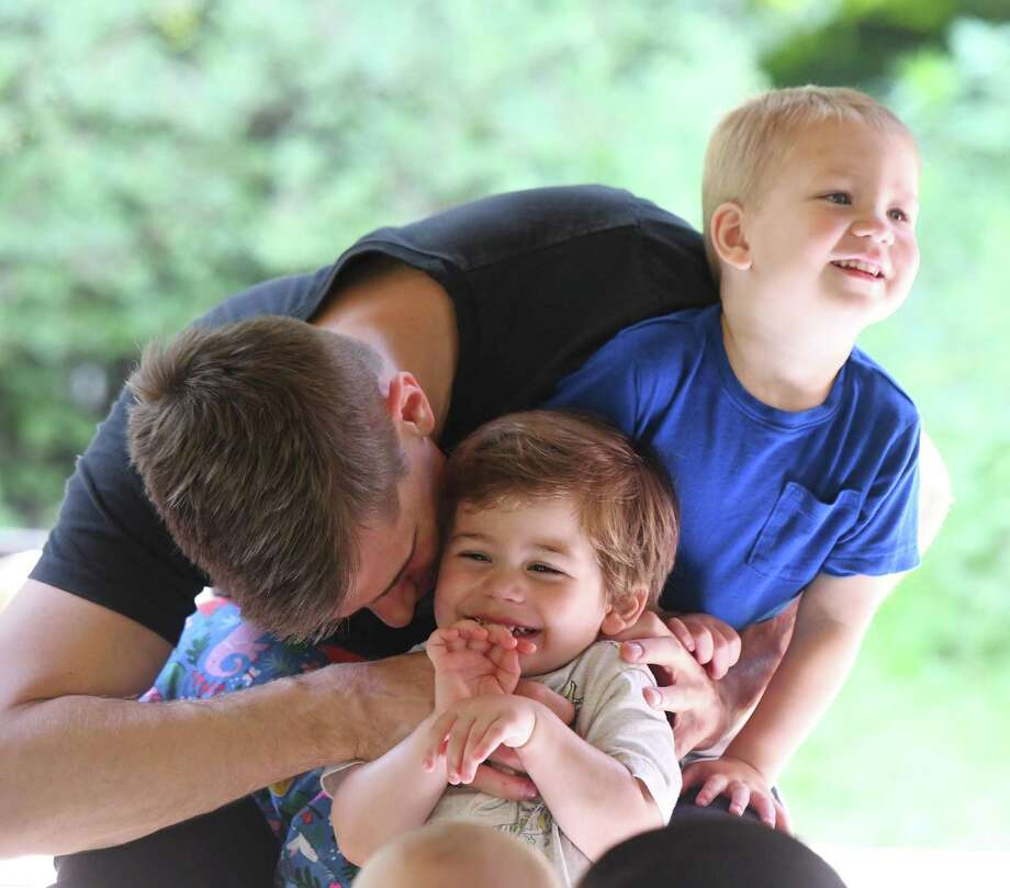 Andres Fernandez cuddles his kids Benecio, right, and Luca, both 2, during Greenwich Library's Stories in the Park children's reading event at the Bruce Park Playground in Greenwich, Conn. Wednesday, July 17, 2019. The interactive book reading and songs entertained a large group of babies, toddlers and preschoolers. The reading under the Bruce Park gazebo occurs every Wednesday at 10:30 a.m. Photo: Tyler Sizemore / Hearst Connecticut Media / Greenwich Time
