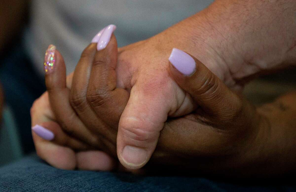 Chris Mock holds his wife's, Kelley, hand as she talks to reporters about her mother, Saron, who died yesterday evening during a drive-by shooting Wednesday, July 17, 2019, in Katy, Texas. The James were driving home on Old Greenhouse Road after her doctor's appointment. She was 62.