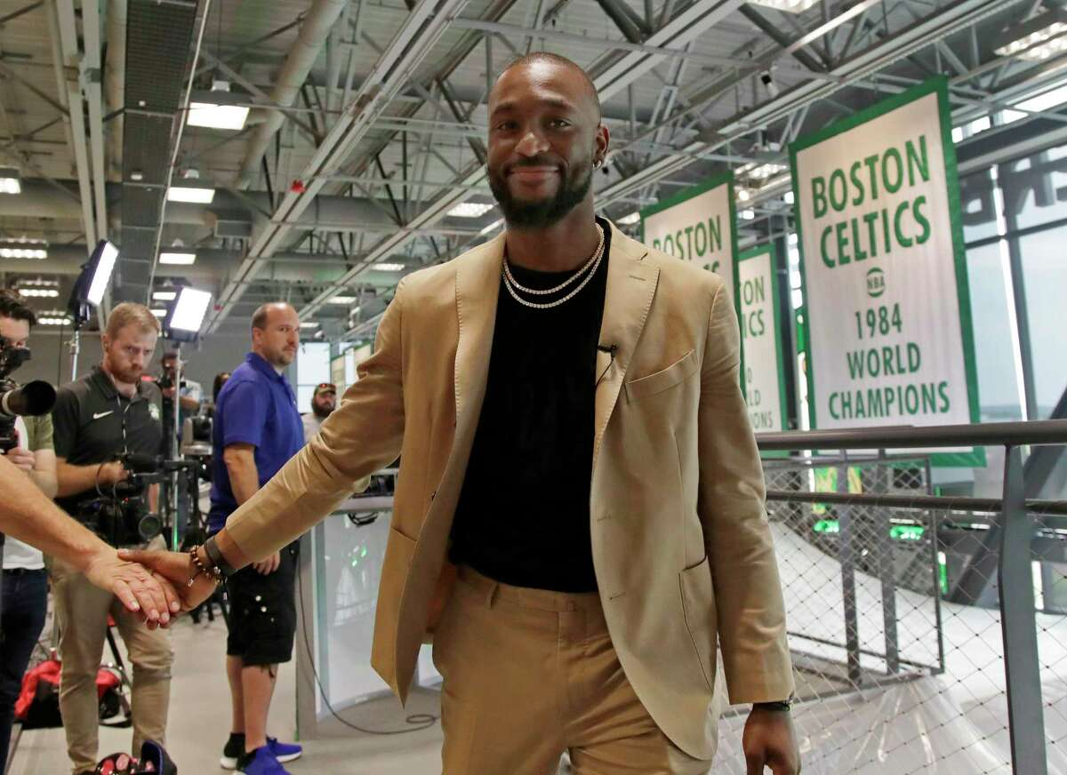 Newly acquired Celtics guard Kemba Walker shakes a hand as he leaves an interview at the Celtics' basketball practice facility on Wednesday.