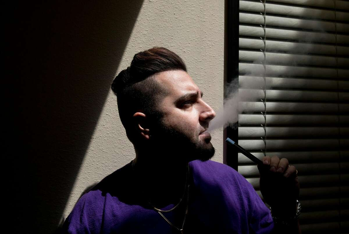 Customer service manager Cyrus Malekzadeh smokes a vape inside Apollo ECigs in Livermore, Calif. Tuesday, July 16, 2019.