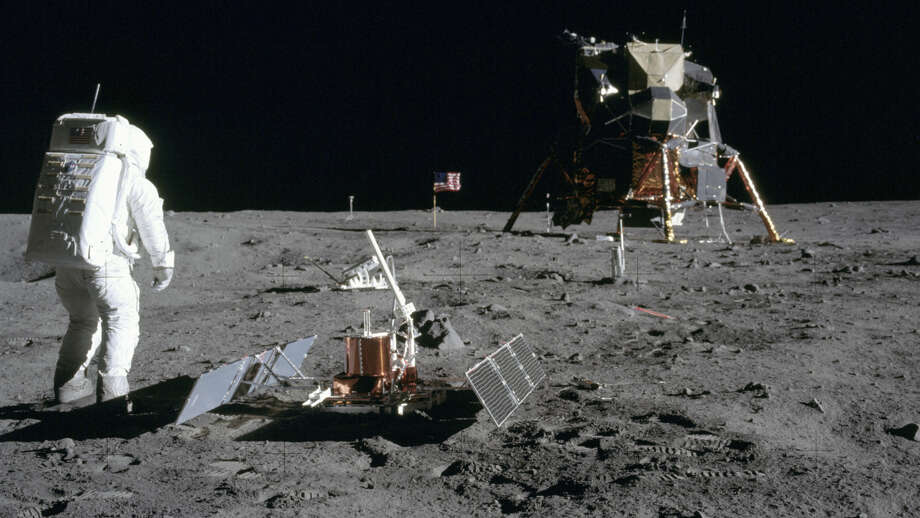 Astronaut Buzz Aldrin is shown just after he deployed the Early Apollo Scientific Experiments Package (EASEP). In the foreground is the Passive Seismic Experiment Package (PSEP); beyond it is the Laser Ranging Retro-Reflector (LR-3); in the center background is the United States flag; in the left background is the black and white lunar surface television camera; in the far right background is the Lunar Module. (NASA)