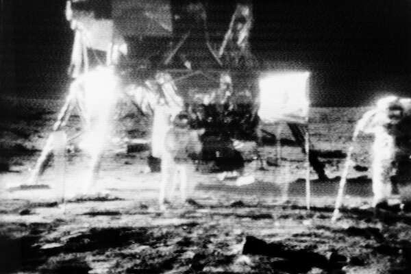 Astronauts Neil Armstrong (center) and Buzz Aldrin (right) are shown standing near their Lunar Module in this black and white reproduction taken from a televised image received at the Deep Space Network (DSN) tracking station at Goldstone, Calif. (NASA)