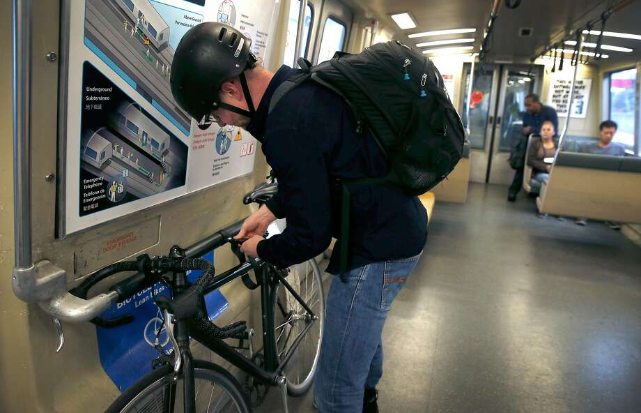 Michael Floyd anchors his bike with straps installed on a BART train after boarding at the El Cerrito del Norte station in El Cerrito, Calif. on Wednesday, July 17, 2019. BART is outfitting every train car with straps to secure bicycles. Photo: Photos By Paul Chinn / The Chronicle
