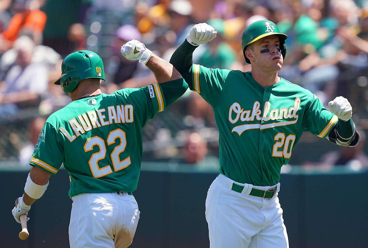 OAKLAND, CA - JULY 17: Mark Canha #20 of the Oakland Athletics is congratulated by Ramon Laureano #22 after Canha hit a solo home run against the Seattle Mariners in the bottom of the six inning at Ring Central Coliseum on July 17, 2019 in Oakland, California. (Photo by Thearon W. Henderson/Getty Images)