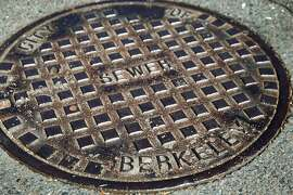 """A manhole cover at Piedmont Street and Garber Avenue in Berkeley, Calif. on Wednesday, July 17, 2019. The Berkeley City Council passed an ordinance to replace gendered language in the city's municipal code with neutral terms, so these would no longer be referred to as """"manhole"""" covers."""